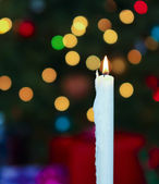 A White Christmas Candle with Blurred Lights — Стоковое фото
