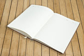 Open book with pen on wood background — Stock Photo