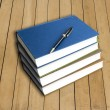 Stock Photo: Blue hardcover books with pen
