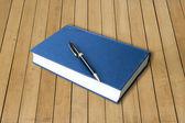 Blue hardcover book with pen — ストック写真