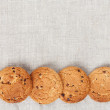 Oatmeal cookies on the texture of flax — Stock Photo