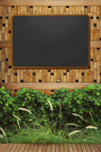 Empty blackboard with wooden frame on wood wall — Stock Photo