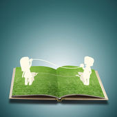 Paper cut of child on grass book — Стоковое фото