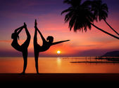 Silhouette of Yoga girls in sunset — Stock Photo