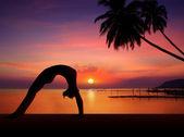 Yoga-kız günbatımı siluet içinde — Stok fotoğraf