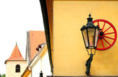 Red wheel and streetlight on a medieval building — Stock Photo