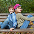 Boy and girl sitting on a bench - Stockfoto