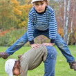 Boy jumping over the girl in autumn park on a grass — Photo