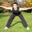 Attractive young man doing exercise in autumn park - Lizenzfreies Foto