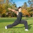 Attractive young man doing exercise in park - Stock Photo
