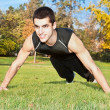 Attractive young man doing exercise in park - Stockfoto