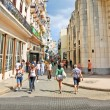 Stock Photo: Cubans walk Calle Obispo street in Havana, Cuba.