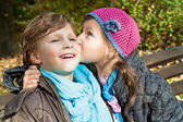 Girl kissing a boy on a bench — Stock Photo