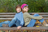 Boy and girl sitting on a bench — Stock Photo