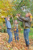 Happy family in autumn forest play with fallen leaf — Stock Photo