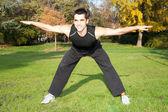 Atraktivní mladý muž dělat cvičení v podzimním parku — Stock fotografie