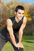 Atraktivní mladý muž dělat cvičení v parku — Stock fotografie