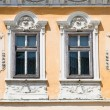 Two windows on orange  wall .  Sibiu, Romania - Stok fotoraf
