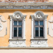 Two windows on orange  wall ,  Sibiu, Romania - Stock Photo