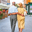 Old couple walking at Piata Sfatului in Brasov, Romania. — Stock Photo