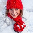 Happy young woman playing snowball fight on the snow day. - Stock Photo