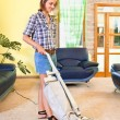 Young beautiful woman with vacuum cleaner at home. - Stock Photo
