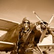 Portrait of beautiful female pilot with plane behind. - Stock Photo