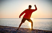 Young attractive man making Thai-chi movements on the beach — Foto Stock