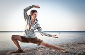 Young attractive man making Thai-chi movements — Stock Photo