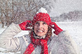 Beautiful woman has a snowball on a red cap — Stock Photo