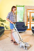 Young beautiful woman with vacuum cleaner at home. — Stock Photo