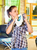 Busy young woman ironing his clothes on self. — Stock Photo