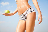 Woman perfect slim body holding an apple. — Stock Photo