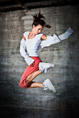 Dancing woman with happy facial expression jumping up — Stock Photo