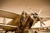 Portrait of beautiful female pilot with plane behind. — Stock Photo