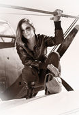 Beautiful girl in black jacket standing on a war aircraft. — Stock Photo