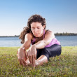 Beautiful young woman doing stretching exercise on green grass. - Stock Photo