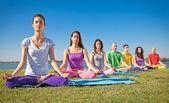 El grupo de jóvenes tiene la meditación en clase de yoga. — Foto de Stock