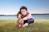 Beautiful young woman doing stretching exercise on green grass. — Stock Photo