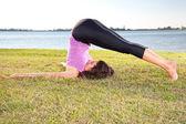 Krásná mladá žena, která dělá jóga cvičení na zelené trávě — Stock fotografie