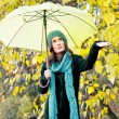 Beautiful young girl under yellow umbrella — Stock Photo #21287519