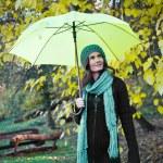 Beautiful young girl under yellow umbrella — Stock Photo #21288157