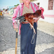 Old farmer with straw hat  holding a rooster. Trinidad, Cuba. - Stock Photo