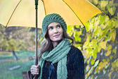 Woman with yellow umbrella smiling — Stock Photo