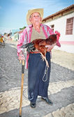 Old farmer with straw hat holding a rooster. Trinidad, Cuba. — Stock Photo