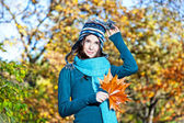 Beautiful girl with leaves on an sunny autumn-day — Stock Photo