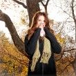 Caucasian woman with cold sneezing into tissue in  park — Stock Photo
