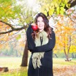 Beautiful girl hold an apple on sunny day in park — Stock Photo