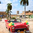 Red oldtimer car in the central square of Trinidad - Stock Photo