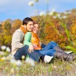 Sweet couple sitting on hill at autumn landscape — Stock Photo #21293989